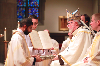 David Verghese receives the Book of the Gospels from Cardinal Sean O'Malley